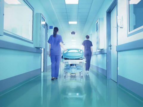 two femaile nurses pushing a hospital bed